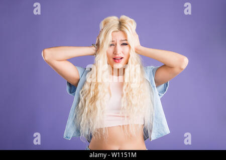 Astonished blonde female with surprised expression listening awesome story, touching head with both hands, received shocking news. Human facial expres - Stock Photo