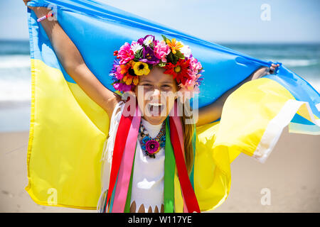 Happy Ukrainian girl holds blue and yellow flag of Ukraine against blue sky and sea background. Ukrainian flag is a symbol of Independence - Stock Photo