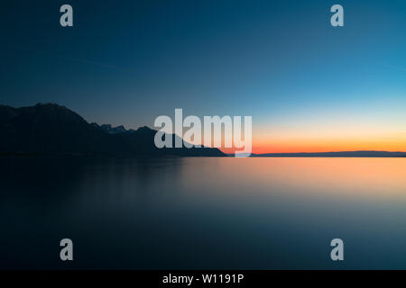 colorful sunset long exposure panorama of Lake Geneva and Swiss Alps mountain silhouette with fading light - Stock Photo