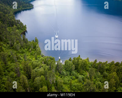 An aerial view of the Teletskoye Lake between the Altai Mountains on which a boat floats to moor to the shore on which there are green trees and other - Stock Photo