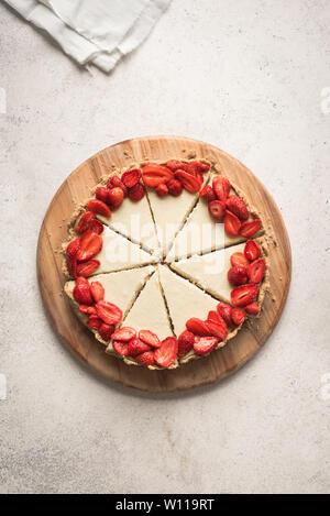 Cheesecake with fresh strawberries for dessert - healthy organic summer berries dessert cheesecake, copy space, top view. Homemade cheese cake. - Stock Photo