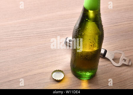 Green bottle with alcoholic beverage on wood table elevated. Horizontal composition. Elevated view. - Stock Photo
