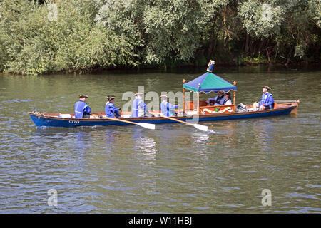 "Hampton Court, London, UK. 29th June 2019. The Tudor Pull is an annual rowing event between Hampton Court Palace and the Tower of London. It includes the transportation of the ""Stela"" (a piece of ancient wooden pipe) on the Queen's Rowbarge Gloriana, which is escorted by a flotilla of small boats. Credit: Julia Gavin/Alamy Live News - Stock Photo"