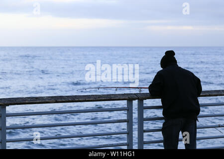 HERMOSA BEACH, USA - MAY 21, 2019: A Fisherman lean against the railing on Hermoasa Beach Pier (Los Angeles). Photographed from behind in the Morning.