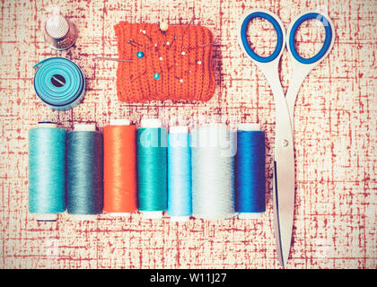 Tools for needlework, red knitted needle pad for sewing, scissors and colored thread coils on brown background with copy space for text - Stock Photo