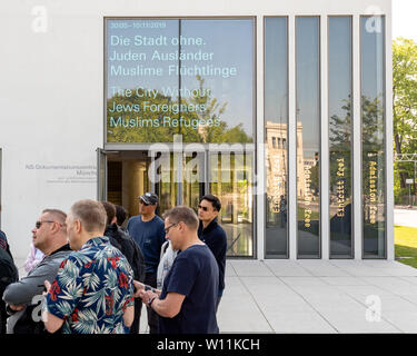 Munich, Bavaria, Germany - May 18, 2019. Tourists lisent to a presentation at the entrance of N-S documentation center for the history of national soc - Stock Photo