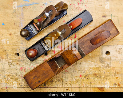 Three woodworking  wooden and metal  smoothing and jack planes on aged woodworking bench grunge surface, shot from above. - Stock Photo
