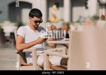 portrait of man in sunglasses sitting in a cafe and drinking coffee on a sunny summer day.