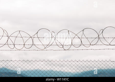 barbed wire fencing against mountains and sky background - Stock Photo