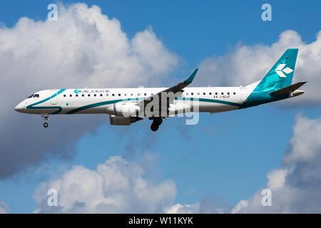 FRANKFURT / GERMANY - AUGUST 12, 2014: Air Dolomiti Embraer 195 I-ADJP passenger plane landing at Frankfurt airport - Stock Photo