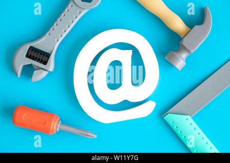 Flat lay of construction tool toys and email sign against blue background minimal creative concept. - Stock Photo