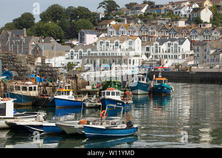 Houses overlooking Brixham Harbour with fishing vessels in the foreground on a sunny day in June. Fishing and tourism are the twon's main industries. - Stock Photo