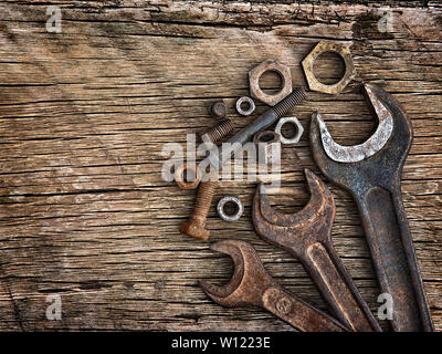 Old wrenches on the nuts and bolts on a wooden grungy background - Stock Photo