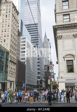 Crowds of people wait to cross 5th Avenue on 42nd Street with the iconic Chrysler Building in the background a few blocks to the east. - Stock Photo