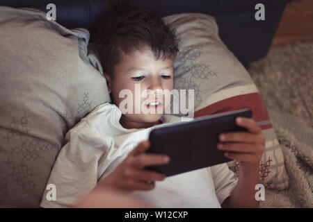 Little boy playing on digital tablet at night in dark bedroom - Stock Photo