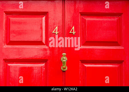 The house number 44 seen on a bright red wooden painted front door with the forty-four in metal digits - Stock Photo