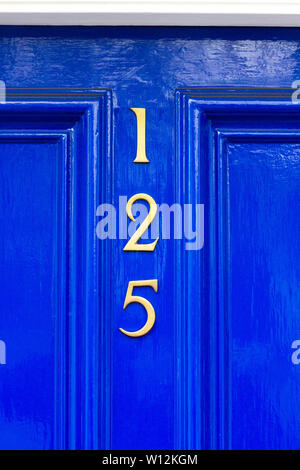 House number 125 with the one hundred and twenty five in gold metal digits arranged vertically on a bright blue carved wooden front door - Stock Photo