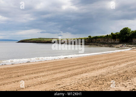 Sun shines during a break in the clouds onto Barry Island's sandy beach, striped by tractor tyre tracks, and the low-lying Friar's point headland. - Stock Photo