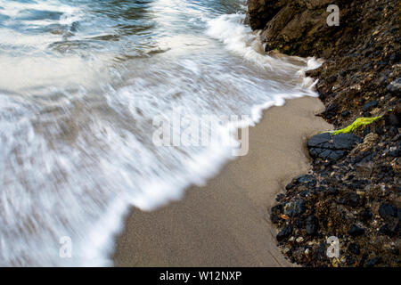 Waves crashing on the rocks at Wood's Cove in Laguna Beach, California. Slow shutter speed. - Stock Photo