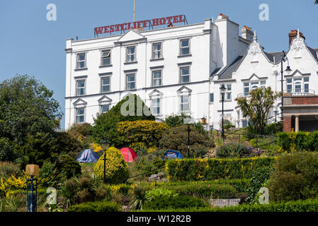 Westcliff Hotel on the cliffs above Southend on Sea seafront Essex, UK with tents of homeless people in the Cliff Gardens. Homelessness Space for copy - Stock Photo