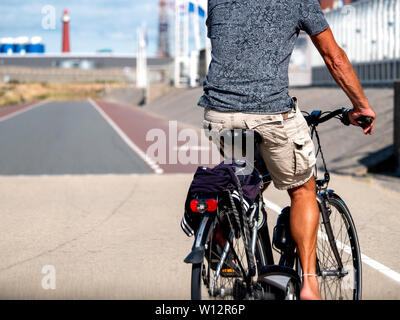 Rear view of man riding a bicycle on driving on the dedicated cycling lane in Netherland Haarlem, Amsterdam The hague - Stock Photo