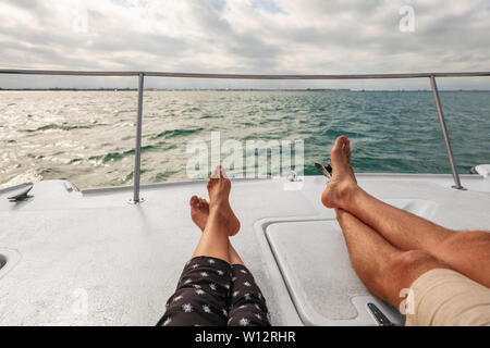 Yacht boat lifestyle couple relaxing on cruise ship in Hawaii holiday . Two tourists feet relax getaway enjoying summer vacation. - Stock Photo
