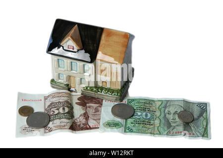 Symbolfoto Haus als Spardose mit DM-Banknoten und Münzen - Stock Photo