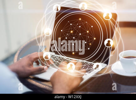 Social network hologram with businessman working on laptop