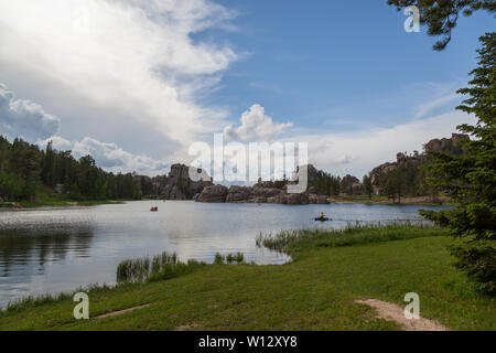 People in small boats enjoy the calm waters of Sylvan Lake with its dynamic granite rock features on the distant shore. - Stock Photo