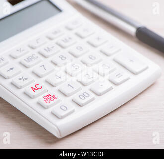 White calculator and pen on bright wooden table, analytics and statistics of financial profit, investment risk concept, copy space, macro, close up