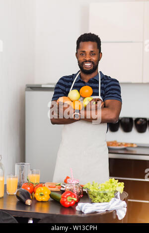 Attractive smiling bearded young dark skinned man wearing apron holding fresh ripe organic oranges, apples and grapefruit, making fruit smoothie, enjo - Stock Photo