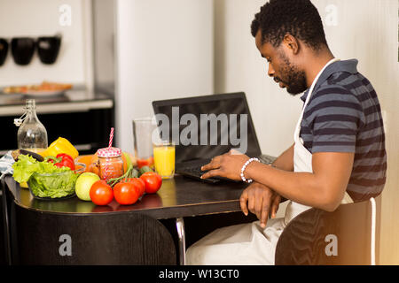 Young bearded african man wearing apron working on laptop, sitting at table in the kitchen, while preparing dinner, drinking fresh fruit juice. Side v - Stock Photo