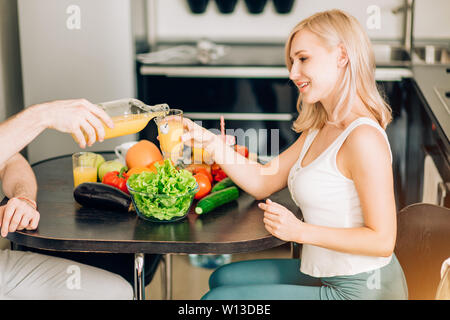 Young couple having breakfast in the kitchen. Man pouring fresh fruit juice in glass for his beautiful blonde girlfriend. Cropped shot. Family, health - Stock Photo