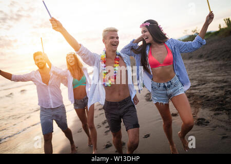 Happy group of friends lighting sparklers and enjoying freedom at beach during sunset - Stock Photo