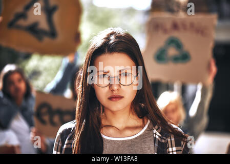 Young woman in eyewear with group of female demonstrators holding signboards while standing outdoors on the road. Ecology concept. Group protesting