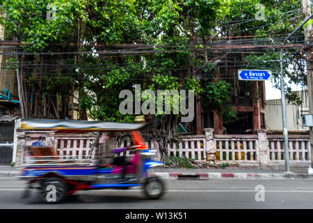 Tuk tuk taxi driving on the streets of Silom district in Bangkok - Stock Photo