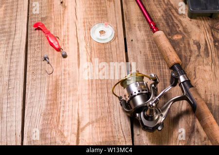 Soft silicone bait and hook for catching predatory fish. Fishing reel with fishing line. - Stock Photo