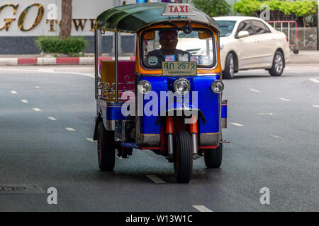 Bangkok, Thailand - April 13, 2019: Tuk tuk taxi driving on the streets of Silom district in Bangkok - Stock Photo