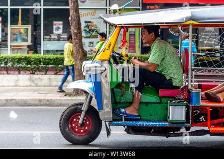 Bangkok, Thailand - April 13, 2019: Tuk tuk taxi driving on the streets of Silom district in Bangkok - Stock Photo