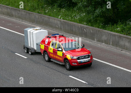 2016 red Ford Ranger XLT 4X4 DCB TDCI Fire & Rescue vehicle with trailer on the M6, Lancaster, UK; Vehicular traffic, transport, modern, saloon cars, north-bound on the 3 lane highway. - Stock Photo