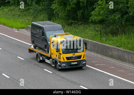 AA Van recovery truck carrying broken down van; Side view of rescue breakdown recovery lorry truck transporter transporting unmarked black van driving along  M6, Lancaster, UK; Vehicular traffic, transport, modern, north-bound on the 3 lane highway. - Stock Photo