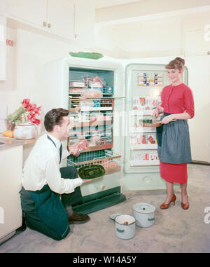 In the kitchen 1950s. A young couple in their kitchen proudly showing their new Frigidaire freezer. ref BV66-4 - Stock Photo