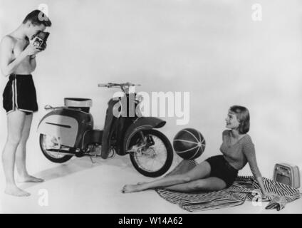 Teenagers of the 1950s. A teenage boy and girl with a brand new Monark Monarsccot model M33. A moped launched 1957 with a futuristic design with the looks of a vespa. It had two gears and costed 945 sek. Sweden 1957 - Stock Photo