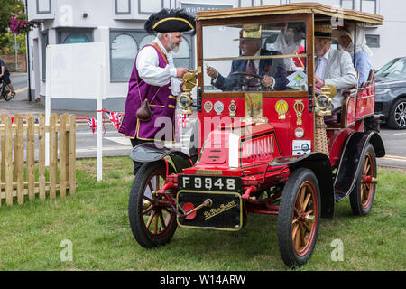 Datchet, UK. 30 June, 2019. Chris Brown, Official Town Crier of the Royal Borough of Windsor and Maidenhead, welcomes the driver of a 1904 De Dion Bouton, the first of many pre-1905 vehicles to arrive on the 48-mile Ellis Journey from Micheldever station near Winchester to Datchet, a reenactment of the first recorded journey by a motorised carriage in England undertaken by pioneer automobilist Hon. Evelyn Ellis in his new, custom-built Panhard-Levassor on 5th July 1895. Credit: Mark Kerrison/Alamy Live News - Stock Photo