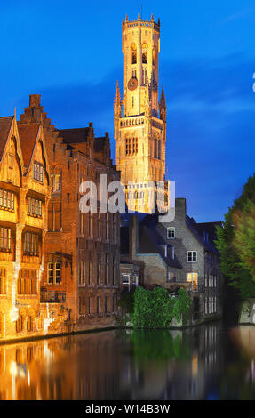 Famous view of Bruges tourist landmark attraction - Rozenhoedkaai canal with Belfry and old houses along canal with tree in the night. Belgium