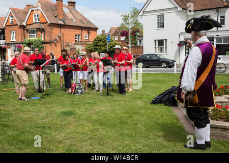Datchet, UK. 30 June, 2019. Chris Brown, Official Town Crier of the Royal Borough of Windsor and Maidenhead, takes a photograph of Romsey Ukulele Group performing before the arrival of pre-1905 vehicles taking part in the 48-mile Ellis Journey from Micheldever station near Winchester to Datchet, a reenactment of the first recorded journey by a motorised carriage in England undertaken by pioneer automobilist Hon. Evelyn Ellis in his new, custom-built Panhard-Levassor on 5th July 1895. Credit: Mark Kerrison/Alamy Live News - Stock Photo