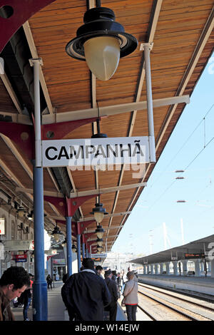 Vertical view of station sign and historic lamp with passengers waiting for train on the platform Campanha Porto Oporto Portugal Europe  KATHY DEWITT - Stock Photo