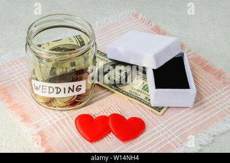 Wedding word, coins and dollar bill in a glass jar near two silk hearts and empty white wedding ring box on a pink fringed napkin. Saving money for we - Stock Photo