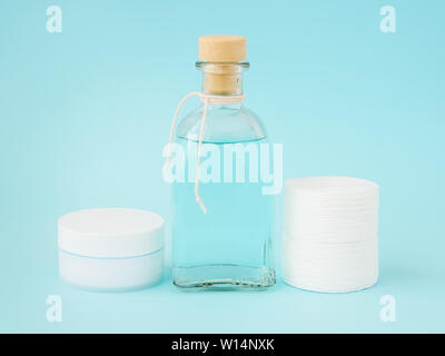 Face cream in white jar, tonic for face skin or makeup remover in a glass bottle and cotton pads on pastel blue background. Hygiene supplies, beauty t - Stock Photo