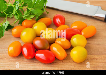 Mix of multicolored cherry tomatoes, parsley and knife on a brown wooden cutting board. Heap of yellow, orange and red small tasty tomatoes. Vegetable - Stock Photo